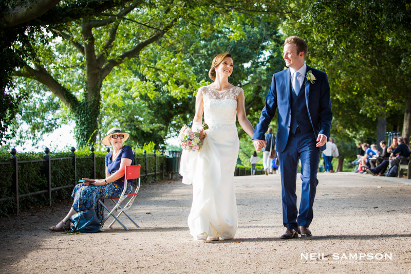 The bride and groom walk holding hands on Richmond hill while a lady looks on