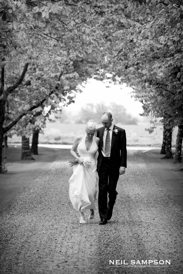 Bride and groom walk along the driveway at South Farm wedding venue