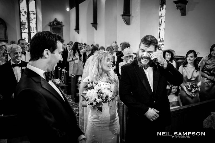 The bearded father of the bride sheds a tear as he gives his daughter away