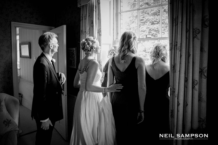 The bridal party look out the window to see who is arriving for the wedding at Micklefield Hall in Hertfordshire