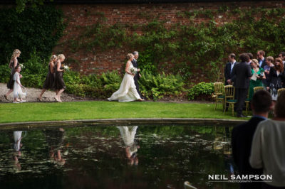 The bridal party are reflected in the lake at this Hertfordshire wedding