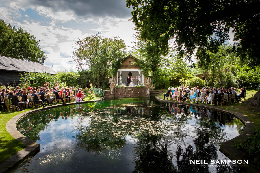 The bride and groom just married can be seen over the pond at Micklefield hall on a sunny day