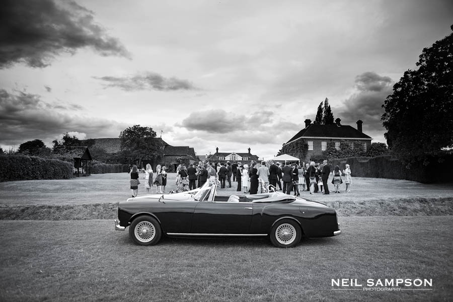 The wedding car is shown in the foreground while the drinks reception takes place at Micklefield Hall in Hertfordshire