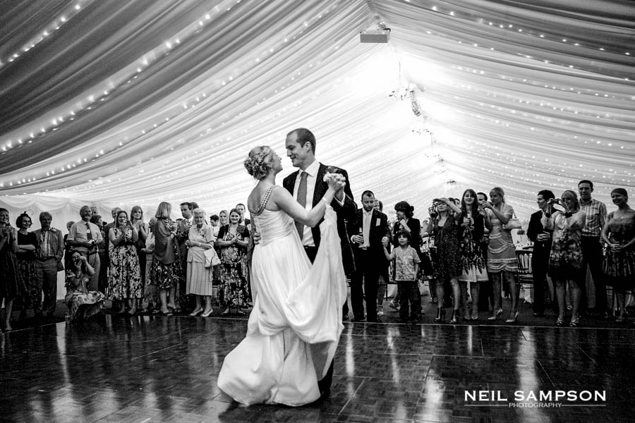 The Bride and Groom enjoy the first dance at Micklefield Hall while the guests look on in the background