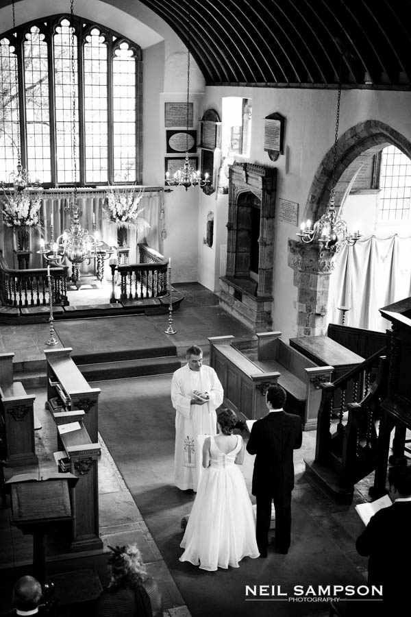 A wedding ceremony shown from above from a balcony at the back of the church