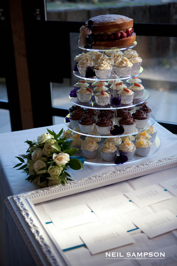 Cupcakes are stacked up with a big chocolate wedding cake on top