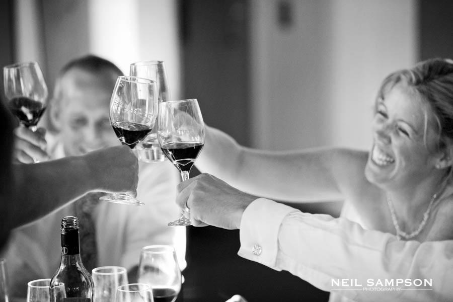 Guests clink their wine glasses together during the wedding breakfast