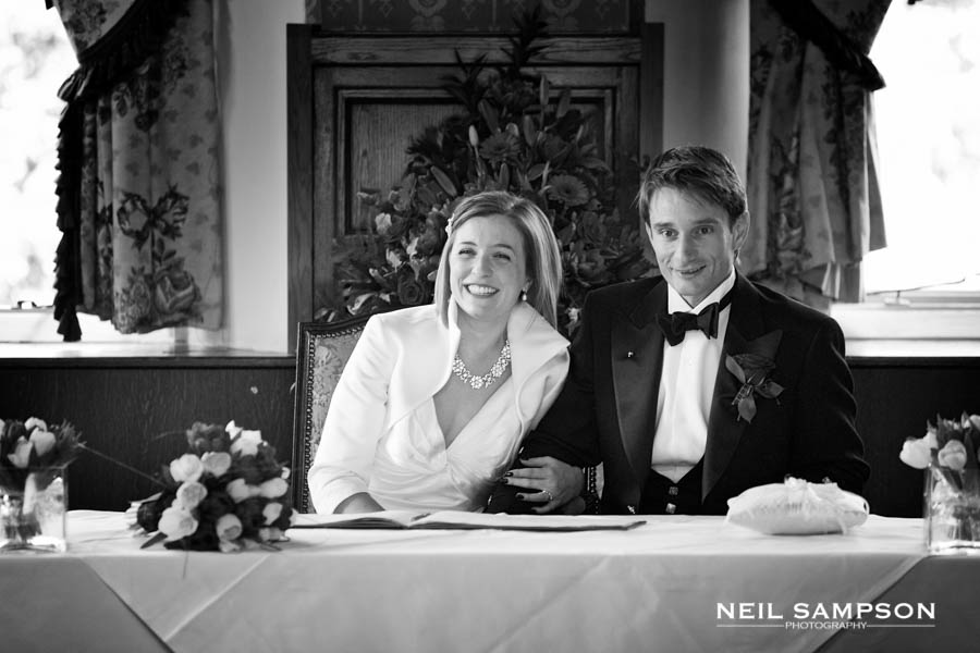 The bride and groom enjoy the moment as they sign the register after the wedding ceremony