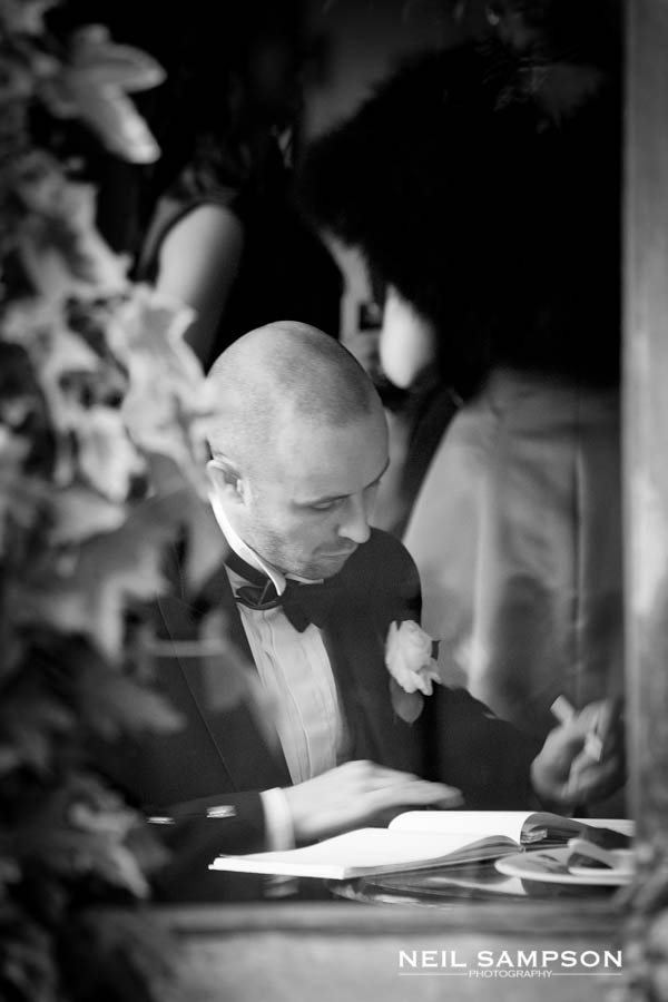 A guest is spotted through a window signing the guest book for the bride and groom