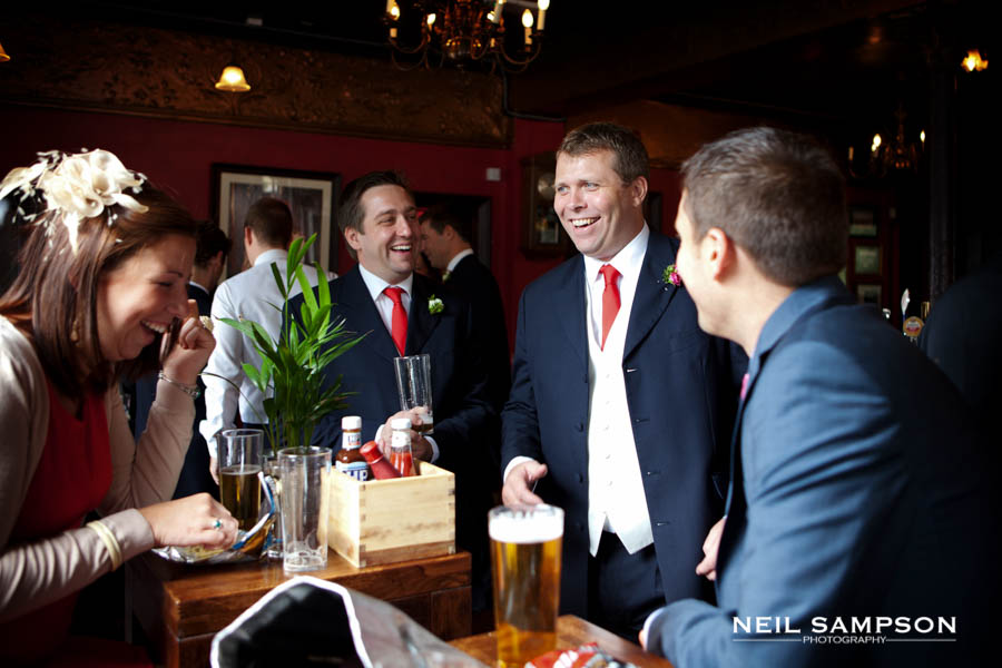 The groom and friends enjoy a drink in the pub before the wedding ceremony