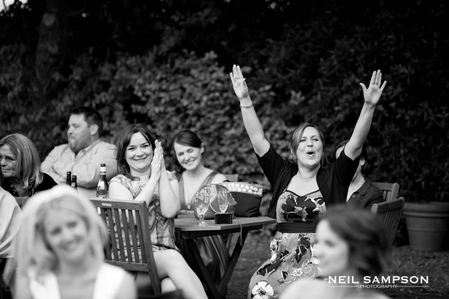 A guest puts her arms in the air during the wedding speeches