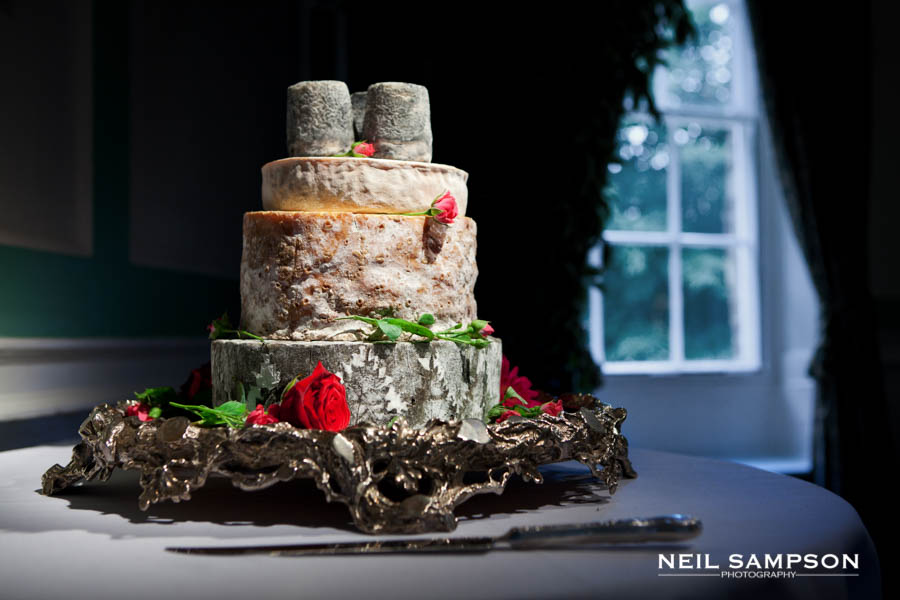 A layered cake made of cheese wheels shown under spotlight