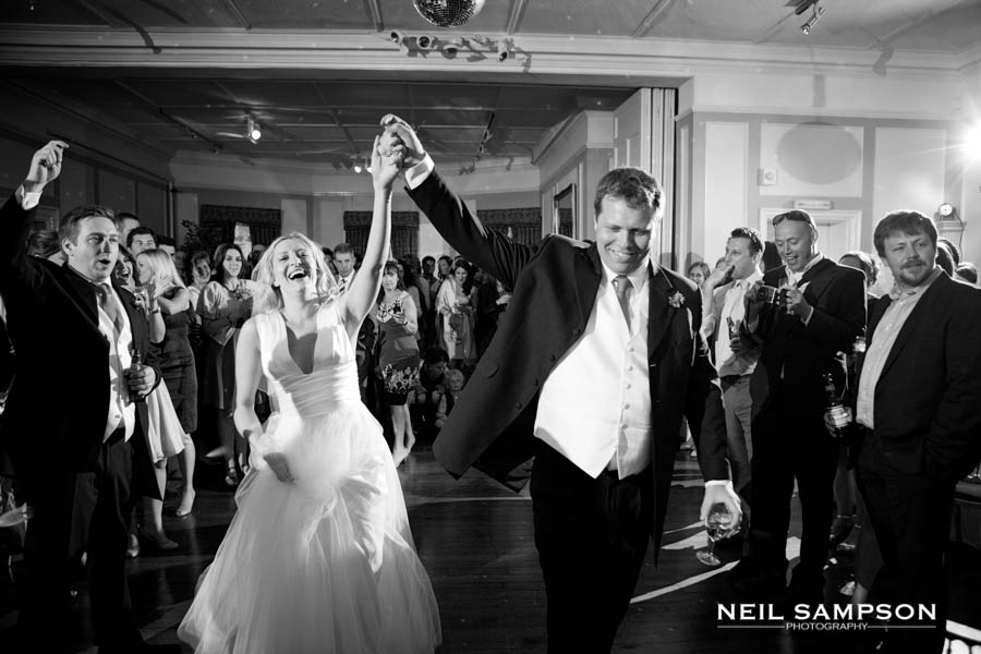 The bride and groom hold their arms up as they enter the dancefloor for the first dance