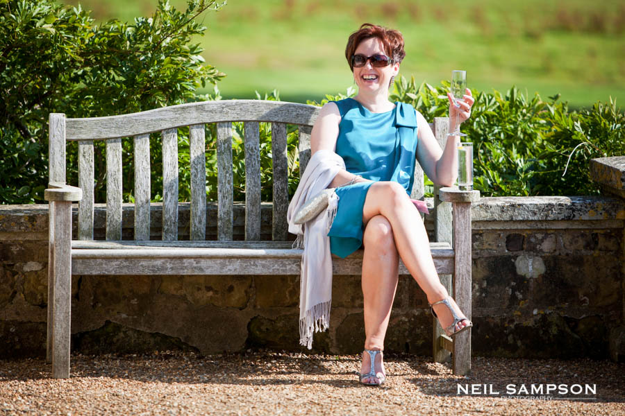 A wedding guest enjoys the reception sat on a bench with a glass of champagne on a sunny day