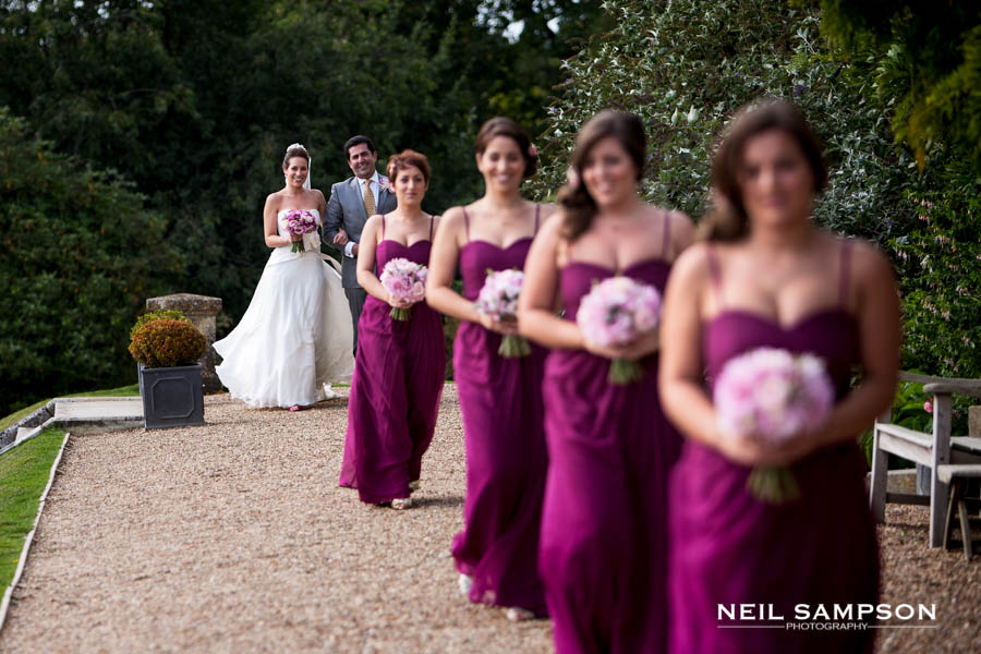 The bridesmaids are in the foreground out of focus and you can see the bride arrive with her father in the background