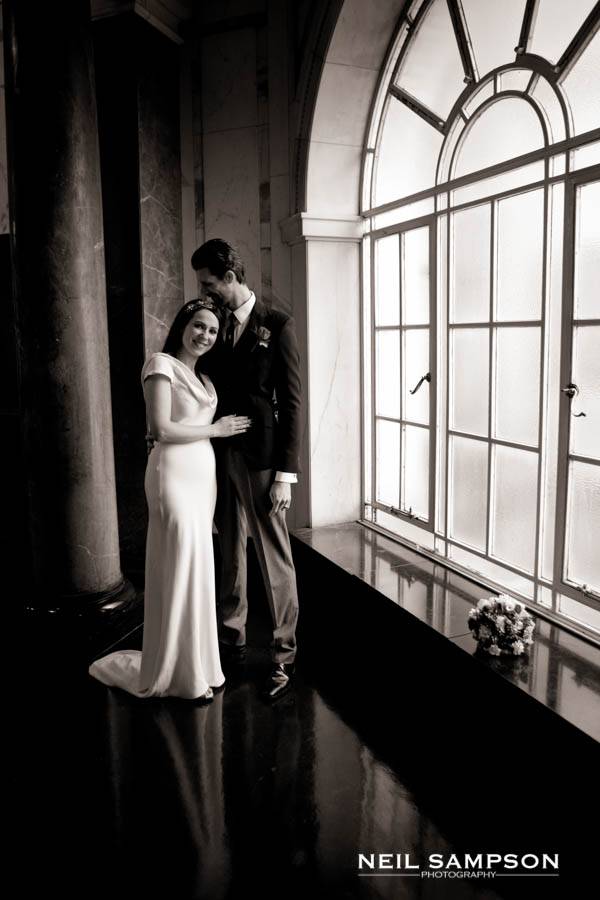The bride and groom pose in front of a large window in City Hall London