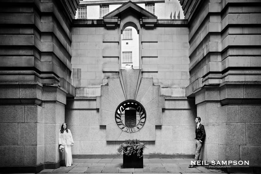 The bride and groom stand in dramatic architecture in this central London wedding