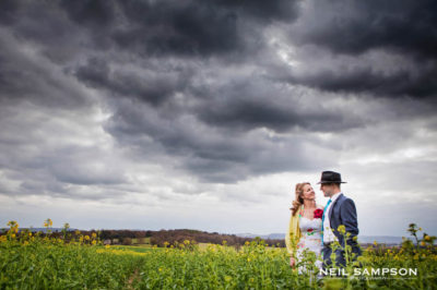 The bride and groom stand in a field with dramatic clouds behind them