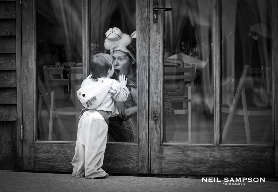 A boy looks at his mother through a window dressed in fancy dress at a wedding
