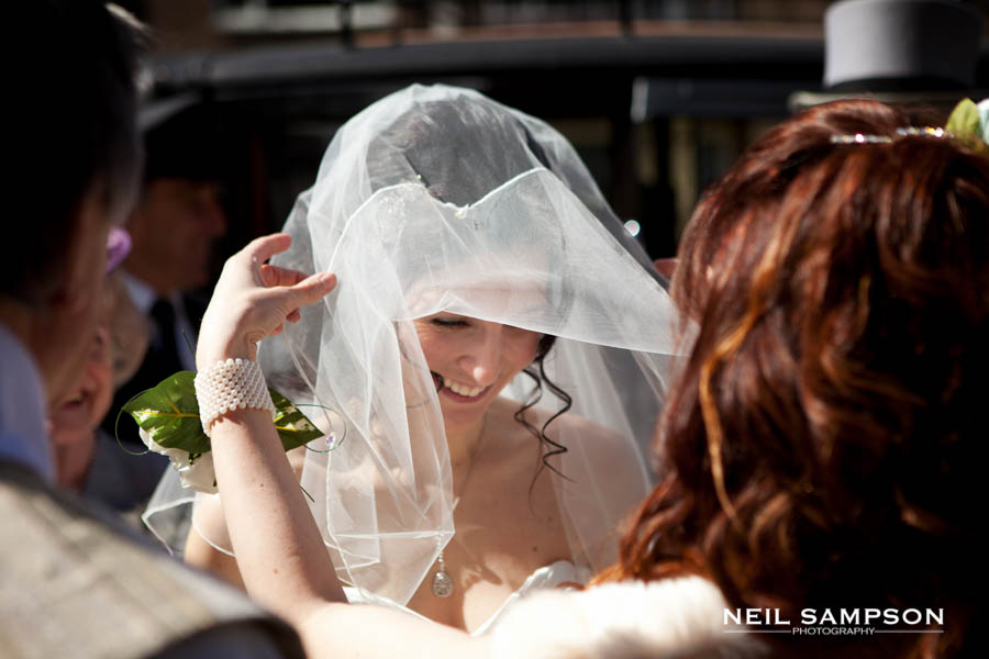 The bridesmaid helps the bride with her veil before the wedding