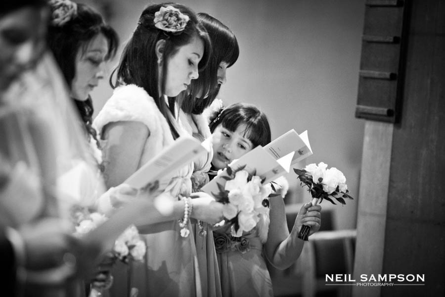 The bridesmaids are lined up in church reading from the hymn book