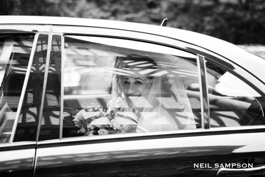 The bride arrives to the wedding by car and you can see Grim's Dyke hotel reflected in the window