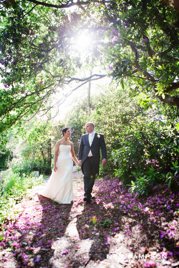 The bride and groom are backit by the sun at Grim's Dyke