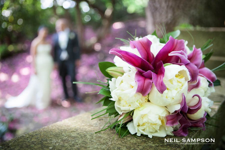 A close up photo of the bride's bouquet as the bride and groom can just be seen in the background
