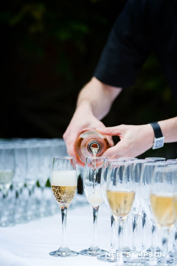 A hotel worker pours champagne as the guests arrive after the wedding for the drinks reception