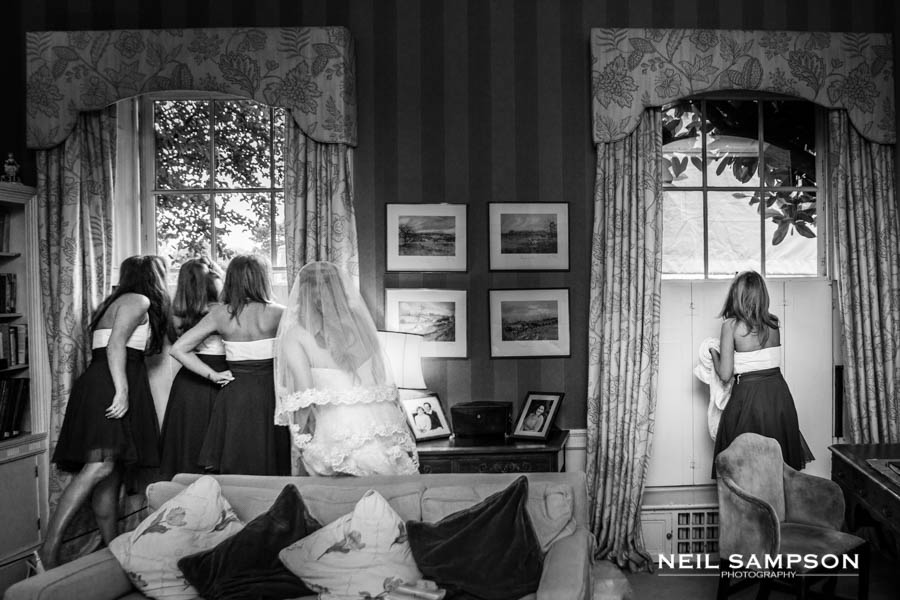 The bride and her bridesmaids sneak a peek at guests arriving for the wedding at Micklefield Hall in Hertfordshire