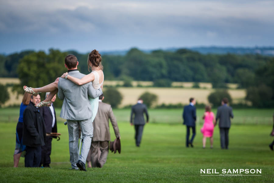 A man carries a woman in his arms on the way to the wedding reception
