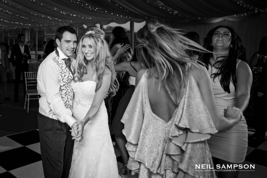 The bride and groom smile at the camera while two guests dance and swing their heads