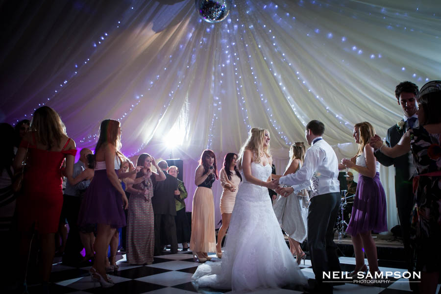 The bride and groom enjoy their first dance in the marquee at Micklefield Hall in Hertfordshire