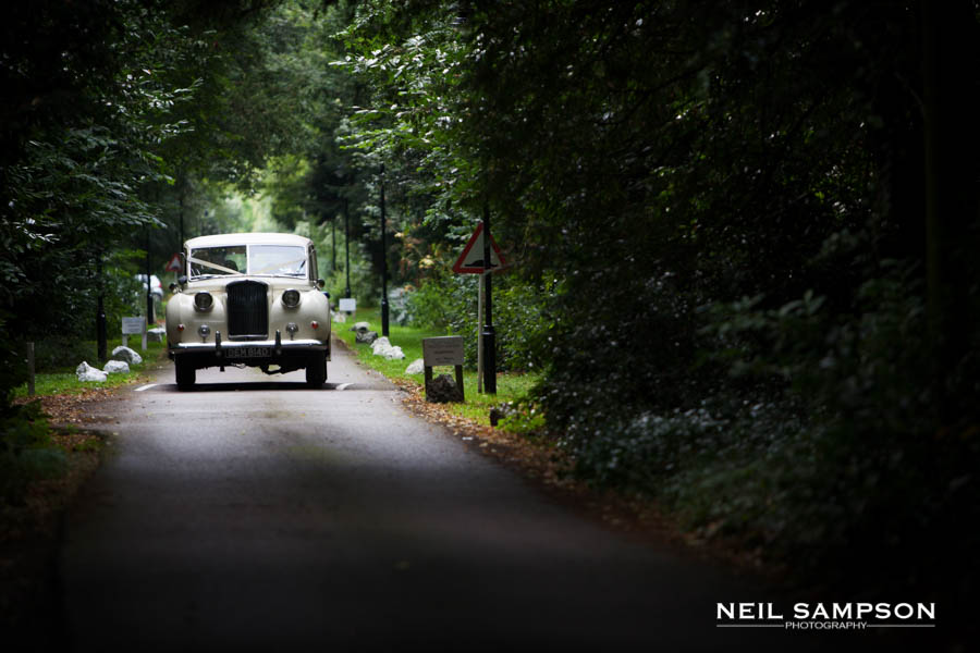 The wedding car comes down the drive at Pendley Manor in Hertfordshire