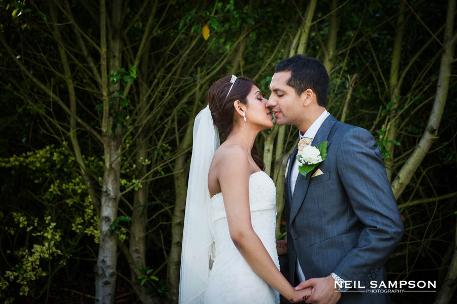The bride and groom kiss and hold hands at Pendley Manor