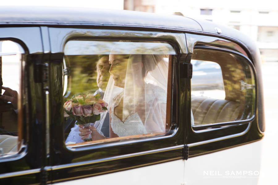 The bride can be seen in the back of the wedding car with her father