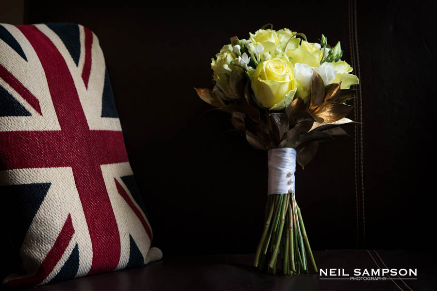 The bouquet of yellow roses stands up close to a union jack cushion