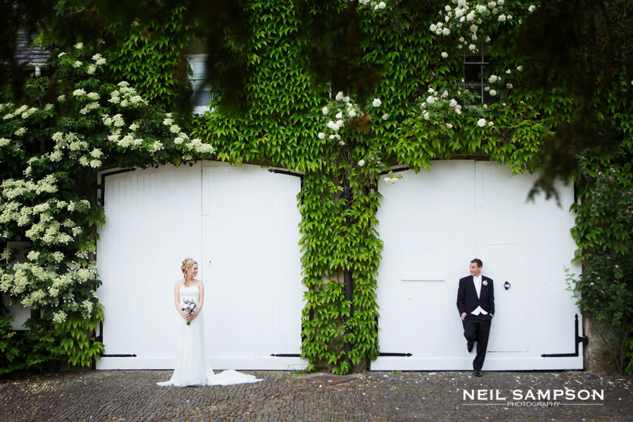 The bride and groom pose in front of large white gates and look at each other at Northbrook Park in Farnham