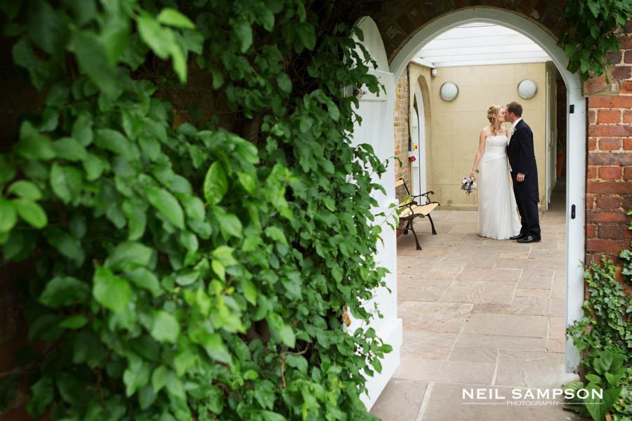 The bride and groom enjoy a private kiss and can be seen through an arch at Northbrook Park in Farnham