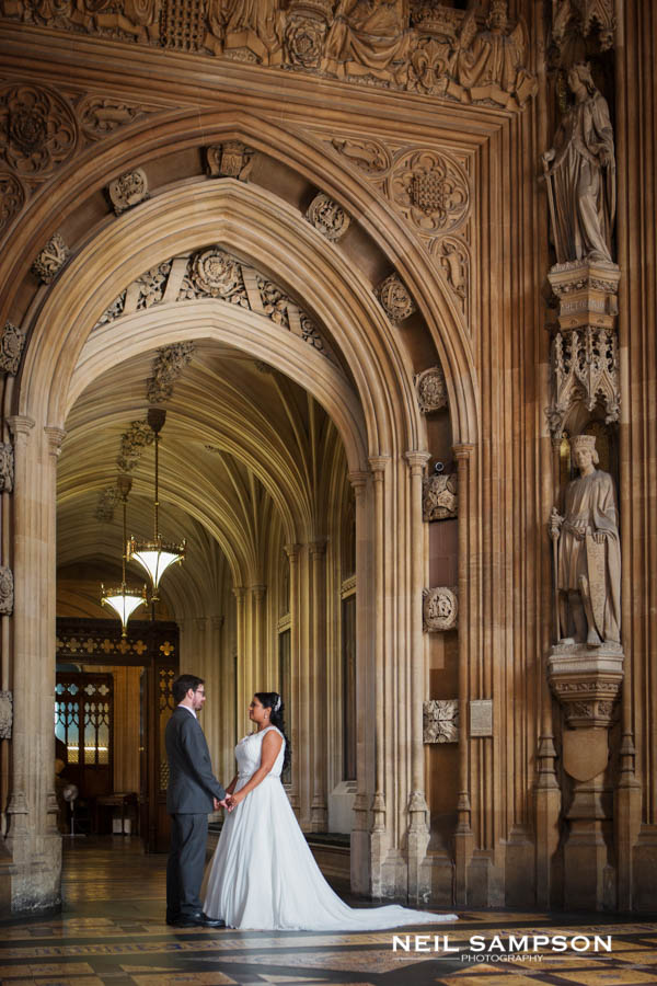 The bride and groom hold hands as they pose for a photo at the houses of parliament after their wedding