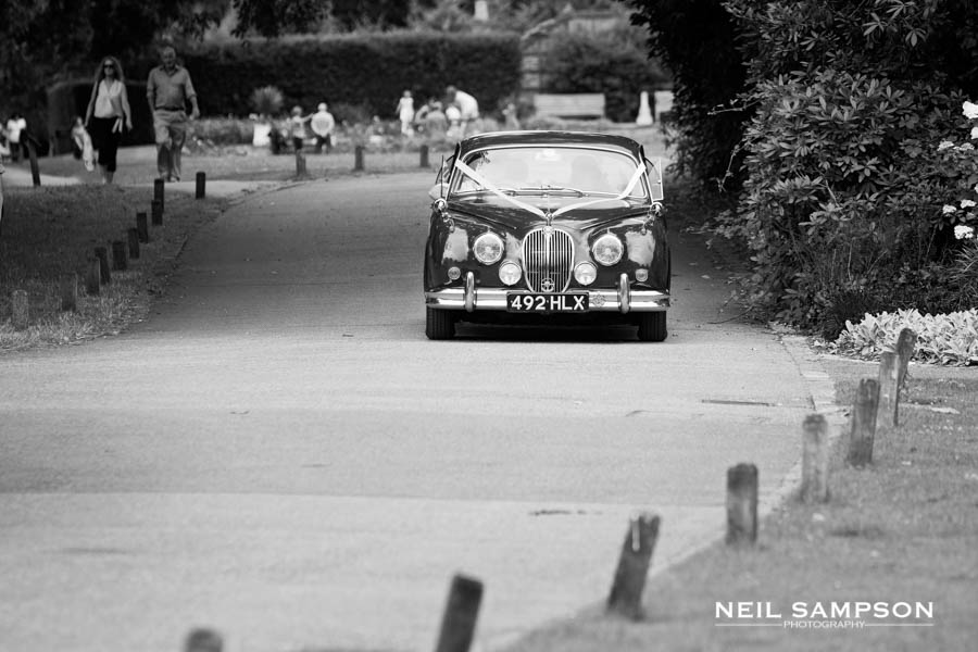 The bride and groom arrive at Pembroke Lodge in their vintage car