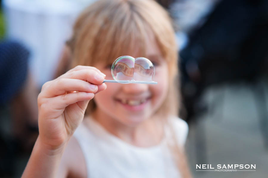 A young girl holds up bubbles in front of her eyes at the wedding reception