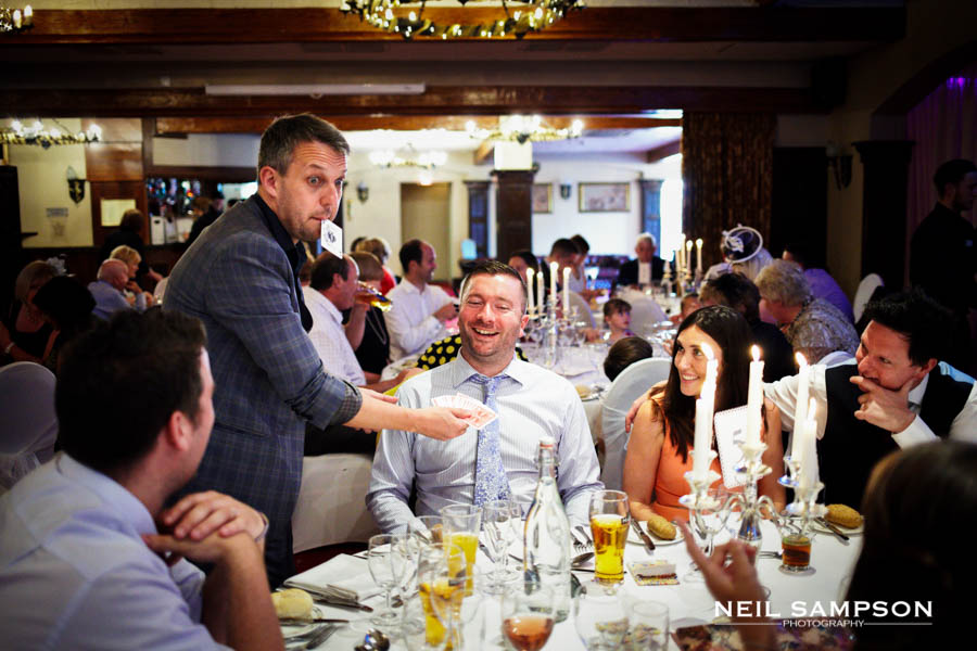 A wedding magician does card tricks for guests at a wedding reception