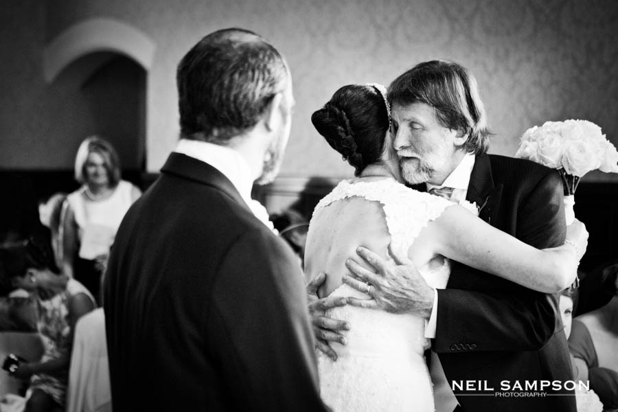 The father of the bride hugs his daughter as he gives her away to her new husband