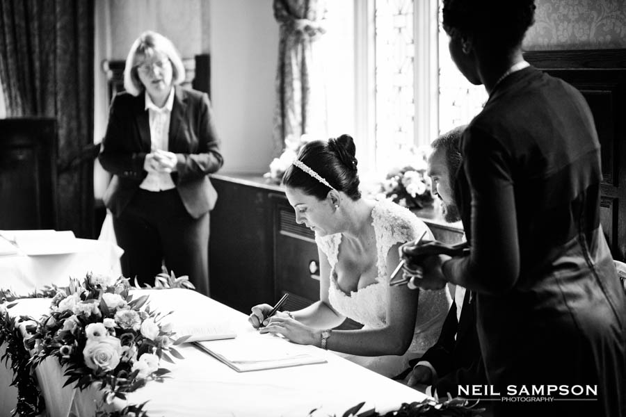The bride signs the register after the ceremony at Grim's Dyke Hotel in Harrow Weald