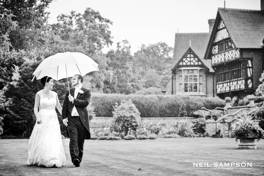 Bride and groom walk with umbrella at Grim's Dyke Hotel