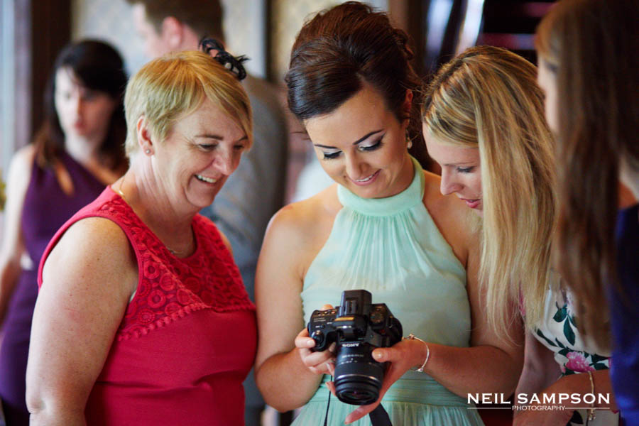 Wedding guests look through their photos on the back of a camera