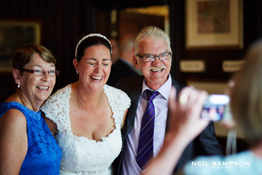 The bride laughs genuinely with her family as her photos is taken by a guest