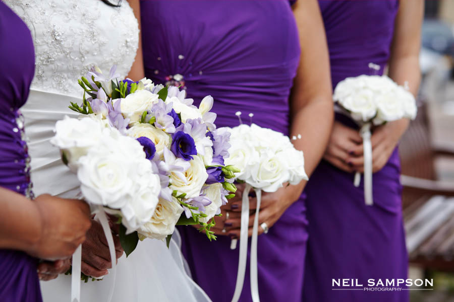A close up photo as the bride and her bridesmaids hold their flower bouquets