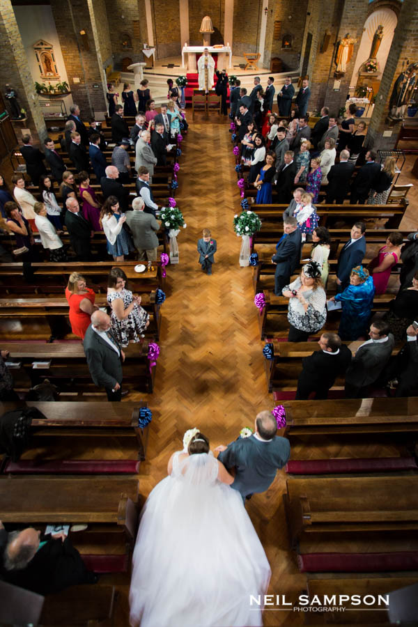 A page boy stands in the aisle as the bride makes her way down the aisle with her father